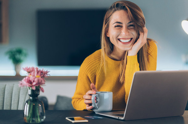 Woman smiling at desk with laptop